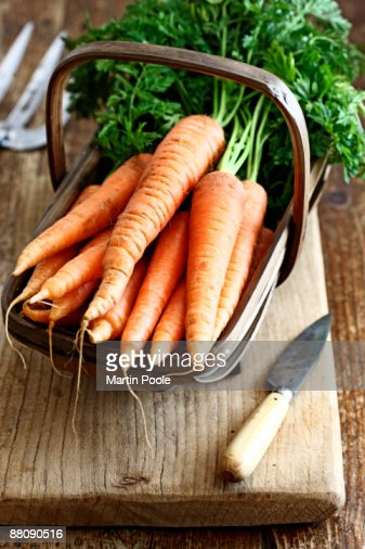Carrots in trug on kitchen table : Stock Photo