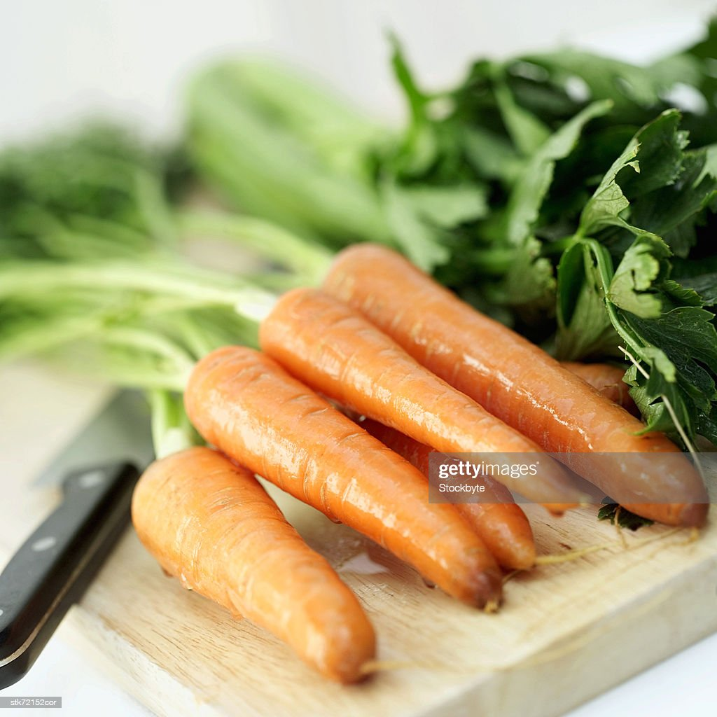 carrots on a wooden cutting board with a knife : Stock Photo