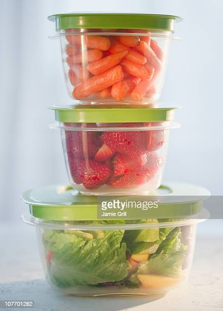 Carrots, strawberries and salad in plastic containers, studio shot