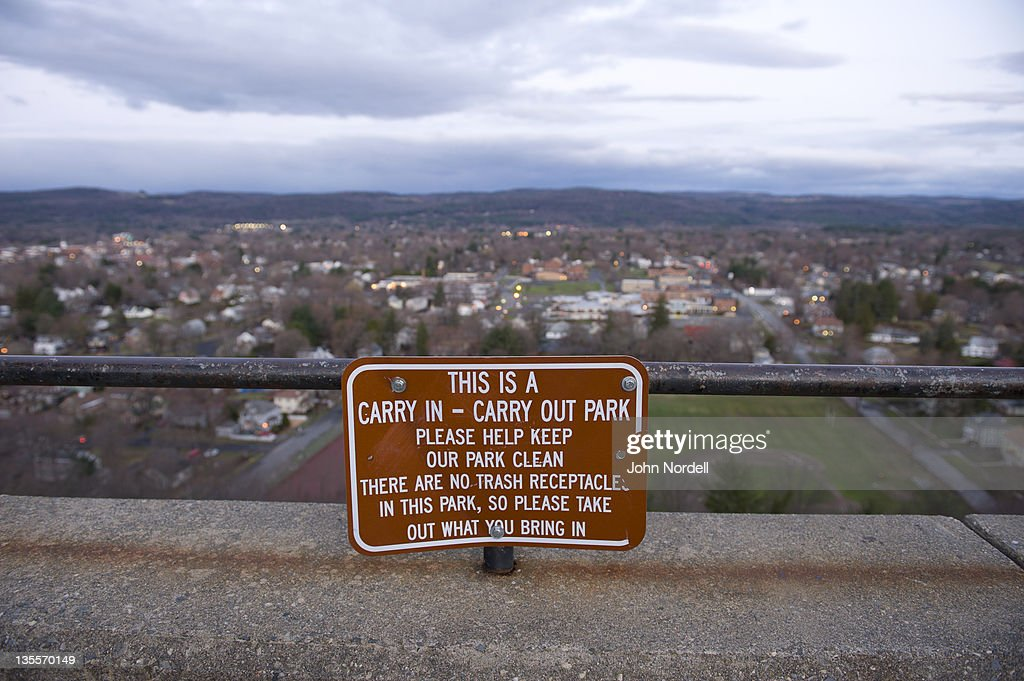 Carry in - Carry out trash sign overlooking the former industrial town of Greenfield, Massachusetts
