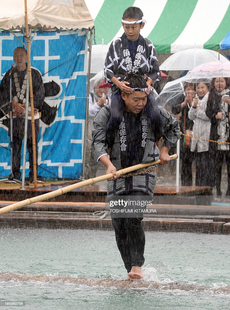 Carrying a boy on his shoulder, a raftsman, a member of the Kiba 'kakunori' preservation society, performs a stunt on a floating square lumber at a local festival in Tokyo on October 20, 2013. The stunt is derived by managing to ride on a floating square lumber during the daily work of lumberjacks during the Edo period (1603-1868).
