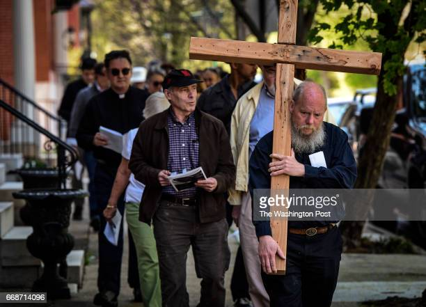 Carrying a cedar cross John Seeley leads a procession of clergy and members of Memorial Episcopal Church on a walk of the Stations of the Cross using...