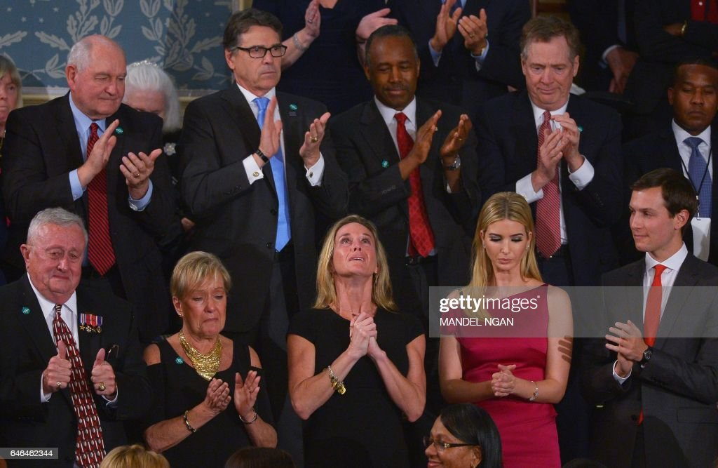 TOPSHOT - Carryn Owens, the wife of slain Navy SEAL William Ryan Owens, looks up while being acknowledged by US President Donald Trump during his address to a joint session of Congress at the US Capitol in Washington, DC on February 28, 2017. /