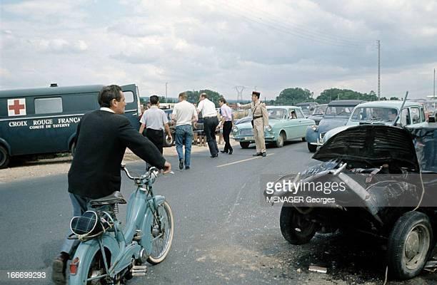 Cars Accident In St Ouen L'Aumone SaintOuen l'Aumône juillet 1966 Sur une route un homme poussant une mobylette passe près d'une voiture gravement...