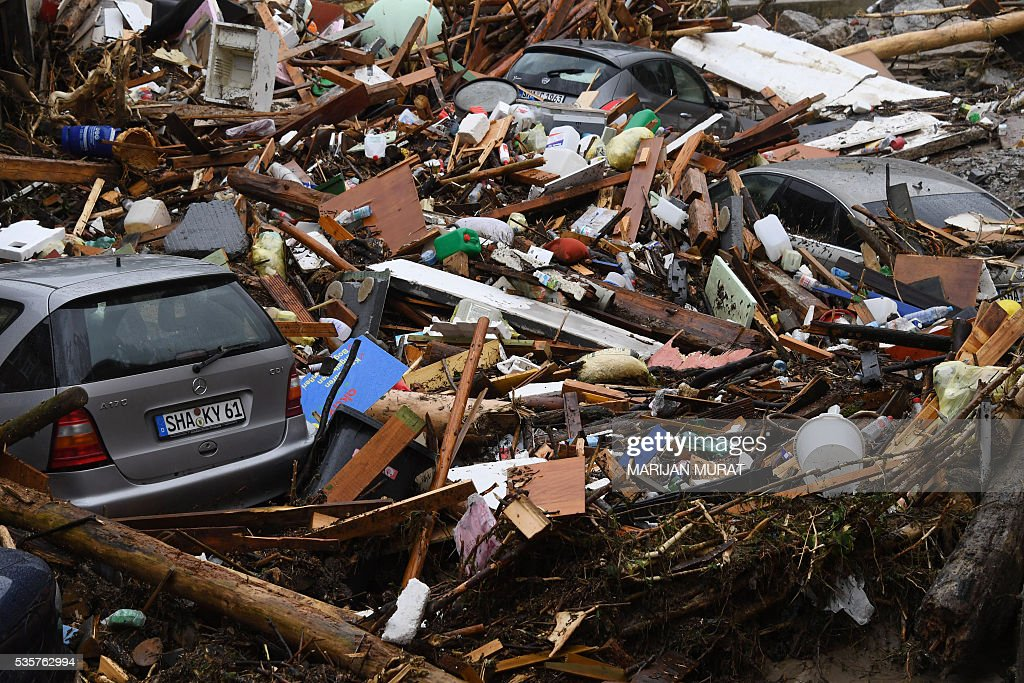 Cars among rubble are pictured on May 30, 2016 in Braunsbach following heavy storm. At least four people died and several more were injured in the south of Germany after torrential storms caused severe flooding, with a third person also feared dead, authorities said on Monday. / AFP / dpa / Marijan Murat / Germany OUT
