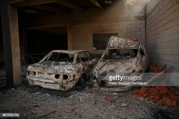 Cars and a house are burnt in the village of Travanca do Mondego on October 17 2017 in Coimbra region Portugal At least 37 people have died in fires...