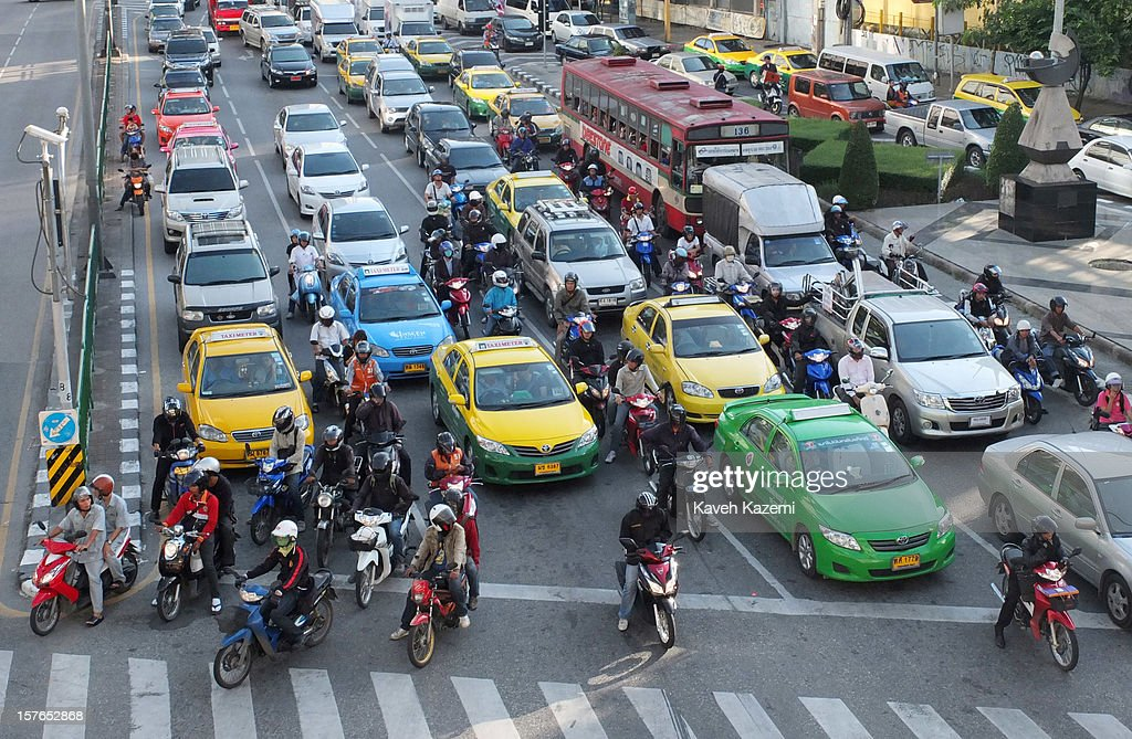 Cars and motorbikes wait behind a red traffic light during the late afternoon rush hour on October 25, 2012 in Bangkok, Thailand.