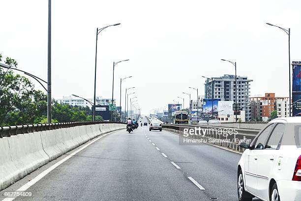 Cars And Motorcycles On Road In City Against Clear Sky