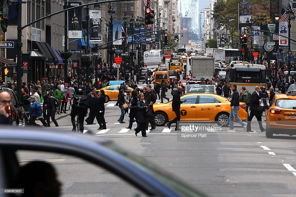 Cars and pedestrians are viewed on a Manhattan Street on November 7 2014 in New York City A new 25 milesperhour speed limit went into effect citywide...