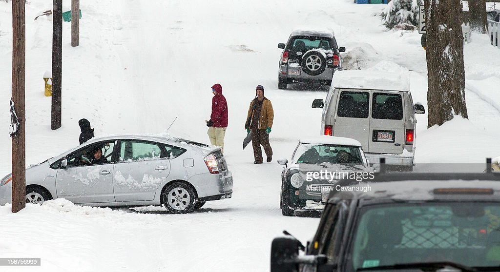 Cars and pedestrians navigate a snowy street on December 27, 2012 in Greenfield, Massachusetts. A serious winter storm that caused tornados in the South on Christmas Day swept across the Northeast on Thursday, bringing snow, sleet, rain and causing dangerous travel conditions.