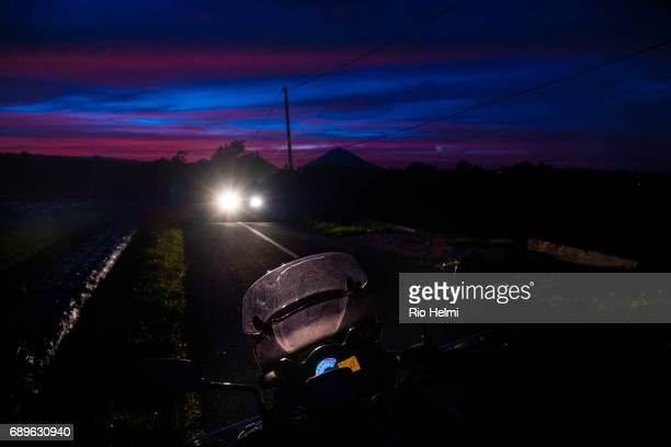 BATURITI BADUNG BALI INDONESIA Cars and trucks at dawn on the ridge road between Bedugul and Kintamani in Bali with Mt Agung in silhouette