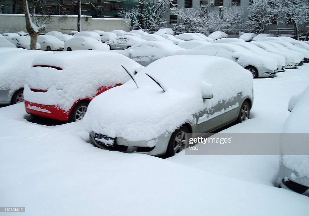 Cars are covered insnow on a snow-covered street on February 19, 2013 in Hefei, China. Heavy snow hit large areas of east China on Tuesday.