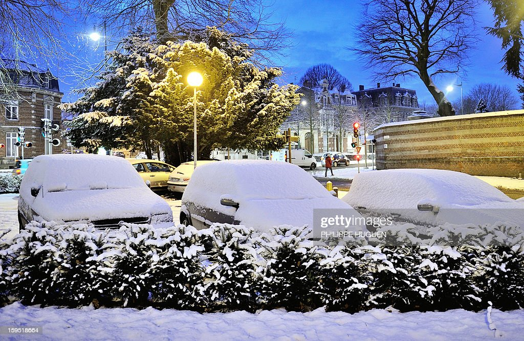 Cars are covered with fresh snow on January 15, 2013 in Arras, northern France, after snow blanketed several French departments. Road traffic is affected by snowfalls in northern and eastern regions.