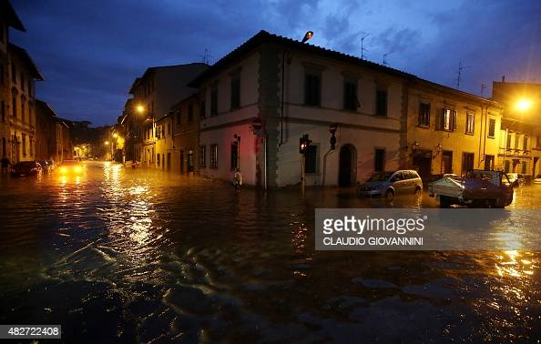 Cars are parked in a flooded road near the Arno river in Florence late on August 1 2015 Some twenty people were wounded on August 1 when a tornado...