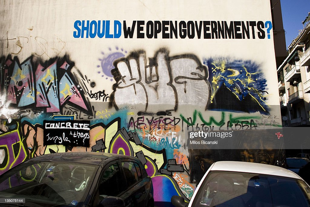 Cars are parked in front of graffiti displayed on a building on December 6, 2011 in Athens, Greece. Graffiti artists throughout the city are expressing the effects of austerity measures that have plagued the community as Greece continues to struggle in debt while lawmakers today are set to pass next year's budget.