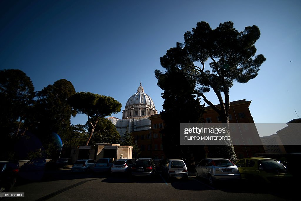 Cars are parked in front of the St.Peter's Basilica at the Vatican City State on February 19, 2013. Pope Benedict XVI will be hosted in the convent of Mater Ecclesiae (Mother of the Church) offering him a substantial four-story modern home complete with contemporary chapel, garden and a roof terrace looking out from a rise dominated by the Holy See's TV transmission tower. Pope Benedict XVI began a week-long spiritual retreat out of the public eye on Monday ahead of his resignation on February 28 with the field of candidates to succeed him still wide open. AFP PHOTO/ Filippo MONTEFORTE