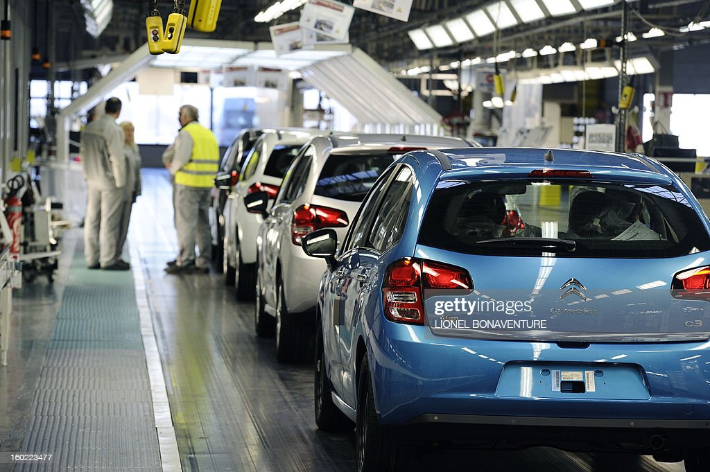 Cars are pictured at an assembly line on January 28, 2013 at the PSA Peugeot Citroen carmaker plant of Aulnay-sous-Bois, a Paris' suburb, as on-strike workers occupy the factory to protest against plans to sell the plant and lay off thousands of employees.