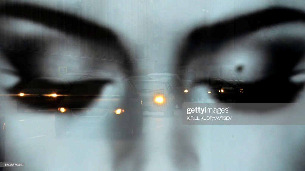 Cars are reflected in a glass cover of a billboard during a traffic jam on Tverskaya street in central Moscow, on February 7, 2013. AFP PHOTO / KIRILL KUDRYAVTSEV