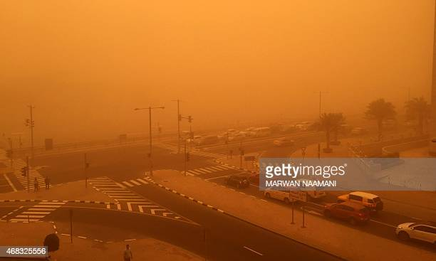 Cars are seen driving amid a sandstorm that engulfed the city of Dubai on April 02 2015 AFP PHOTO / MARWAN NAAMANI