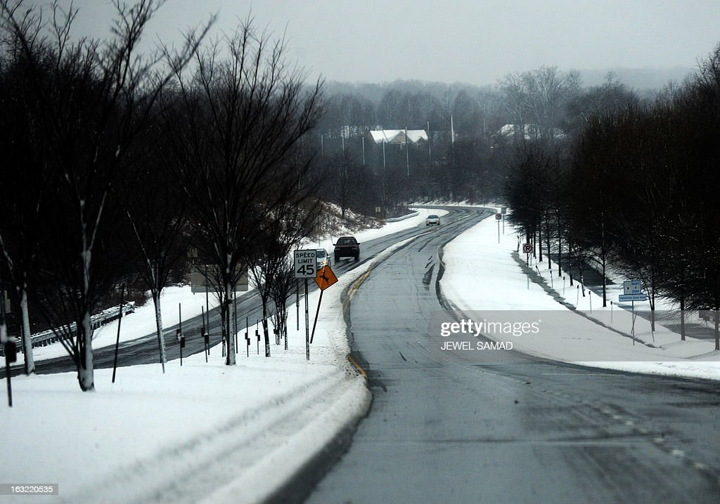 Cars are seen driving during a snow storm in Silver Spring, Maryland, on March 6, 2013. A massive winter storm pounding the northern US on March 6, grounded 2,600 flights, closed hundreds of schools and made roadways and highways impassible. At least four people were reportedly killed in accidents on icy and snow covered roads and highways. AFP PHOTO/Jewel Samad