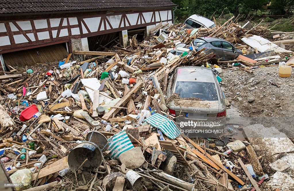 Cars are seen on May 31 2016 amidst of rubble piled up by the floods after a thunderstorm in Braunsbach southern Germany Cleanup efforts started...