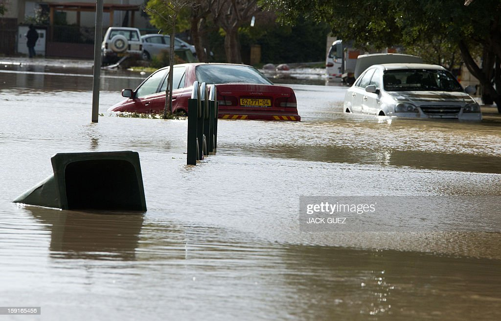 Cars are stuck in a flooded car park due to heavy rains overnight in Beit Hefer, near the Mediterranean coastal city of Netanya, north of Tel Aviv, on January 9, 2013. Israel and the Palestinian territories have been lashed by heavy rain and high winds since January 6, which has caused flooding across the region. AFP PHOTO / JACK GUEZ