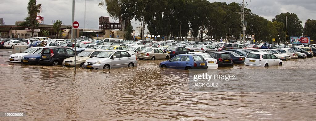 Cars are stuck in a flooded car park in the Meditrranean coastal city of Netanya, north of Tel Aviv on January 6, 2013. Adverse weather continued in Israel, after an unusually blustery weekend. There were considerable delays on rail lines on the coast, with train travel disrupted between Haifa and Tel Aviv in both directions. AFP PHOTO / JACK GUEZ