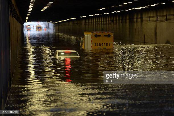 Cars are submerged by floodwater in Beijing on July 20 2016 At least one person was killed and 34 missing as torrential rain pounded northern China...