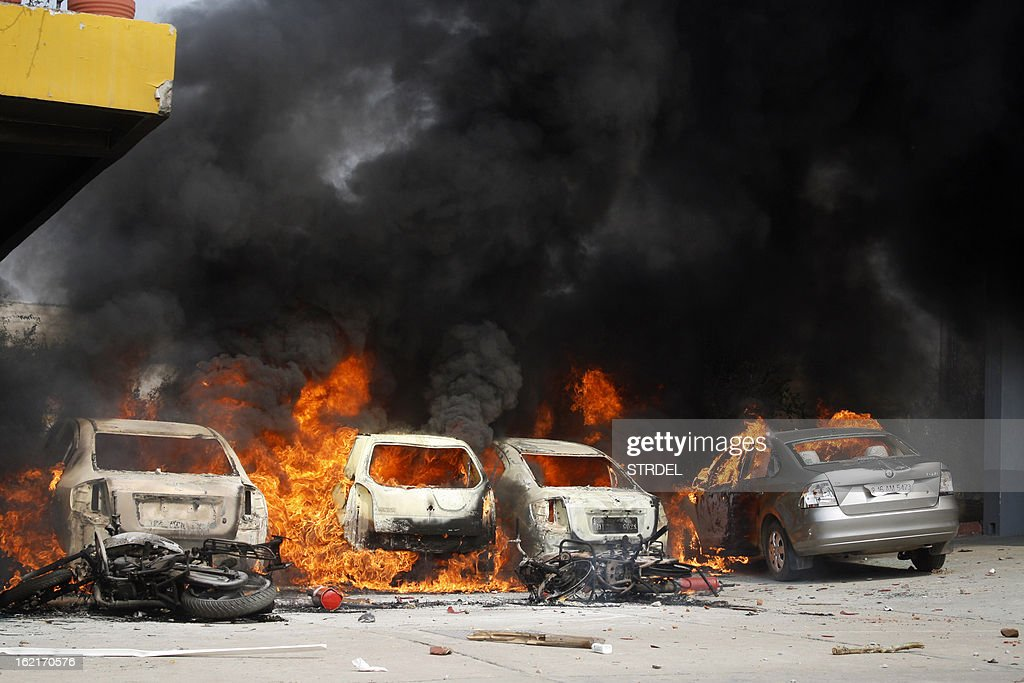 Cars burn in an Indian factory parking lot during a trade union strike in Nodia on the outskirts of New Delhi on February 20, 2013. Cars were burnt and factories were stoned when violence broke out at the all-India trade union strike. Millions of India's workers walked off their jobs in a two-day nationwide strike called by trade unions to protest at the 'anti-labour' policies of the embattled government. Financial services and transport were hit by the strike called by 11 major workers' groups to protest at a series of pro-market economic reforms announced by the government last year, as well as high inflation and rising fuel prices.