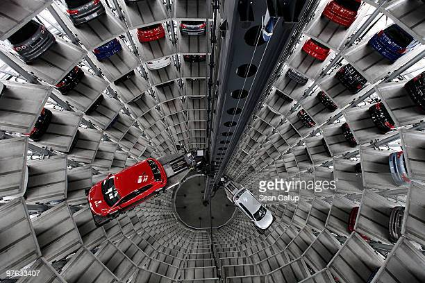 Cars by German automaker Volkswagen AG stand parked in one of two towers at the Autostadt customer reception center at the Volkswagen factory on the...