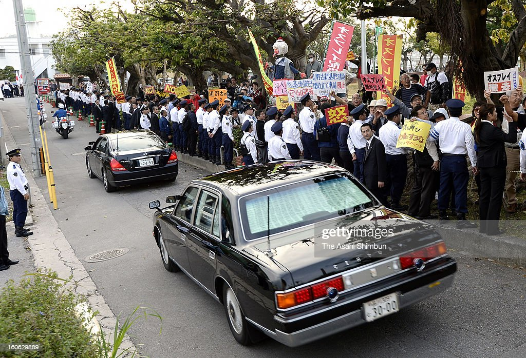 Cars carrying Japanese Prime Minsiter Shinzo Abe to inspect the U.S. Marine Corps Futenma Air Station run while police officers stand guard against protesters on February 2, 2013 in Ginowan, Okinawa, Japan. Abe visits Okinawa for the first time after taking office in December.