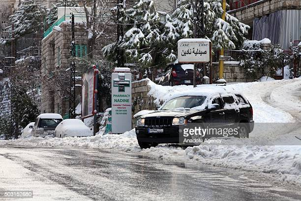 Cars covered in snow pass through a street at Bhamdoun town in Beirut Lebanon on January 2 2016