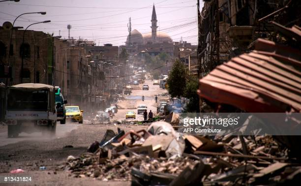 Cars drive along a damaged street in west Mosul on July 12 a few days after the government's announcement of the 'liberation' of the embattled city...
