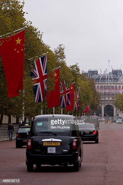 Cars drive along The Mall which is lined with The British Union Jack flag and the Chinese Wu Xing Hong Qi flag ahead of the Chinese State Visit on...