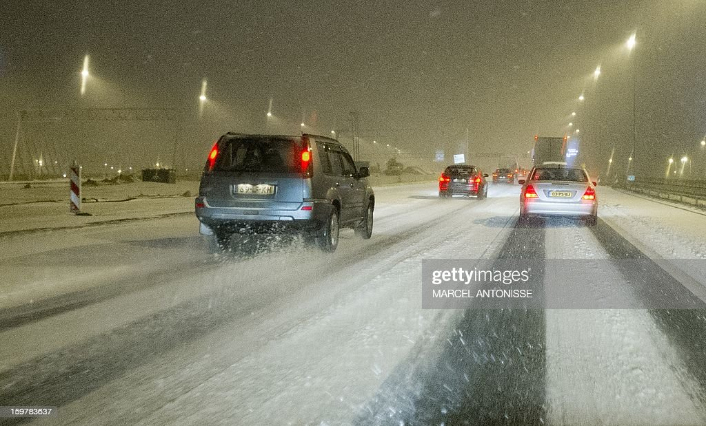 Cars drive carefully over a slippery A10 highway near Amsterdam on January 20, 2013. Snowfalls were reported in major parts of the country.