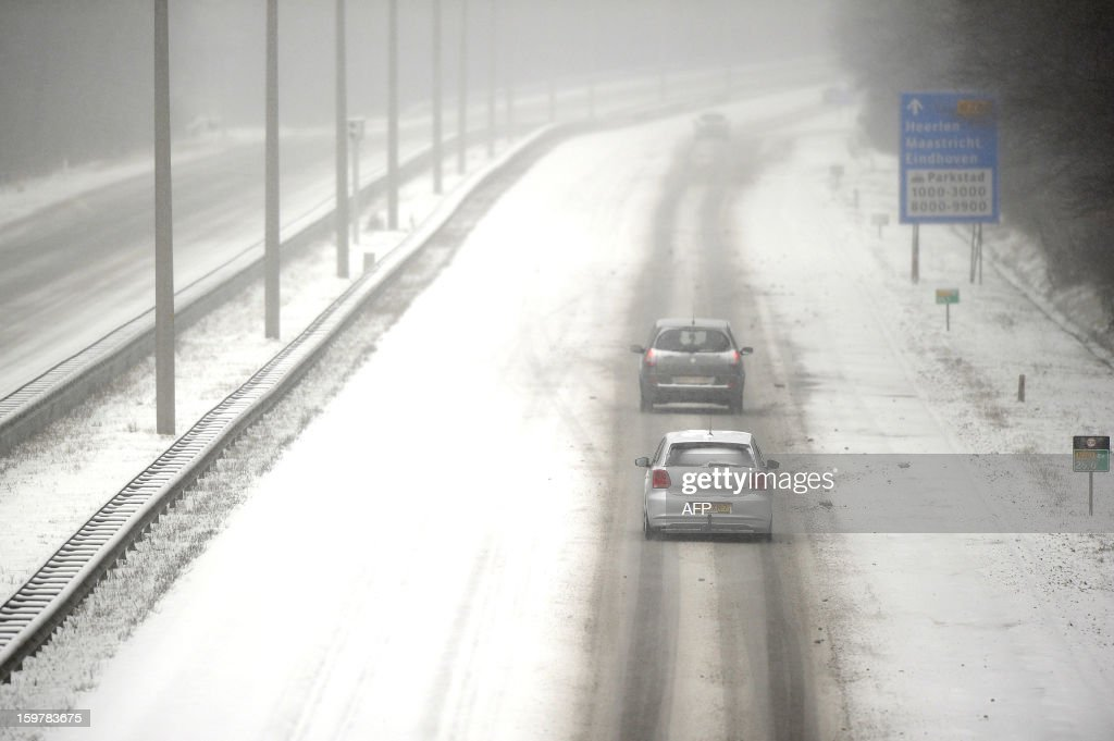 Cars drive carefully over a slippery A10 highway near Heerlen on January 20, 2013. Snowfalls were reported in major parts of the country. AFP PHOTO / ANP / MARCEL VAN HOORN - NETHERLANDS OUT -