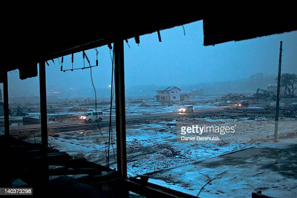 Cars drive down a stretch of road in a neighbourhood ravaged by last year's tsunami on March 2 2012 in Ishinomaki Japan As the oneyear anniversary...