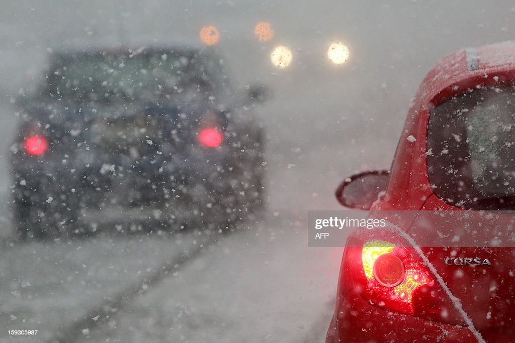 Cars drive during a snow storm on January 11, 2013 in Luebeck, northern Germany.