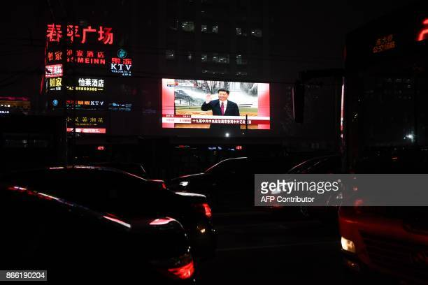 TOPSHOT Cars drive near a screen showing news coverage about Chinese President Xi Jinping in Beijing on October 25 2017 Chinese President Xi Jinping...