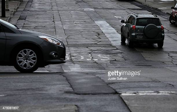 Cars drive on a street with cracked asphalt on February 26 2014 in San Francisco California During a visit to St Paul Minnesota US President Barack...