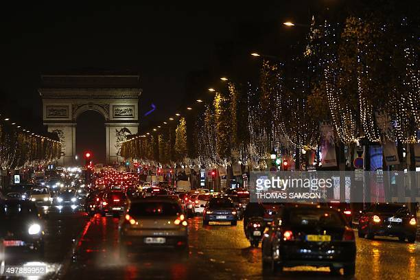 Cars drive on the Avenue des Champs Elysees boulevard illuminated with Christmas lights on November 19 2015 in Paris AFP PHOTO / THOMAS SAMSON