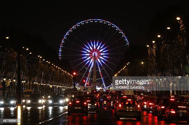 Cars drive on the Avenue des Champs Elysees boulevard near the ferris wheel at the Place de la Concorde square which is illuminated with the French...