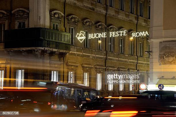 Cars drive pass the Piazza Venezia under a banner reading 'happy holidays' in central Rome on December 27 2015 Local authorities decided to ban cars...