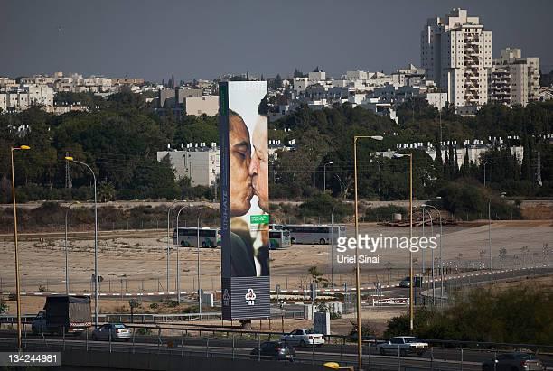 Cars drive past a Benetton Group SpA billboard advertising a composite image of US President Barack Obama kissing Venezuela's President Hugo Chavez...