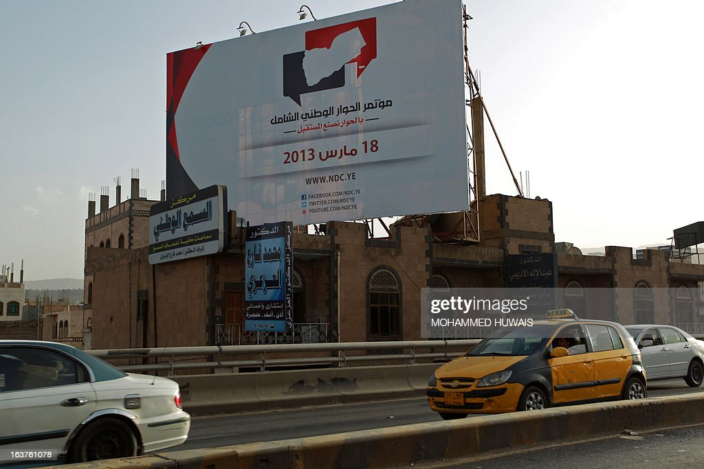 Cars drive past a billboard advertising Yemen's national dialogue conference in Sanaa on March 14, 2013. Yemen, the only country where an Arab Spring revolt led to a negotiated settlement, is to launch a UN-backed national dialogue on March 18, aimed at drawing the state's divisive players towards a reconciliation.