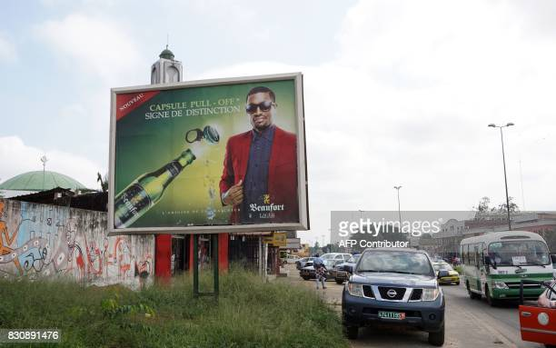 Cars drive past a billboard displaying an advertisement for Beaufort lager beer in Abidjan on July 13 2017 On posters and huge billboards around the...
