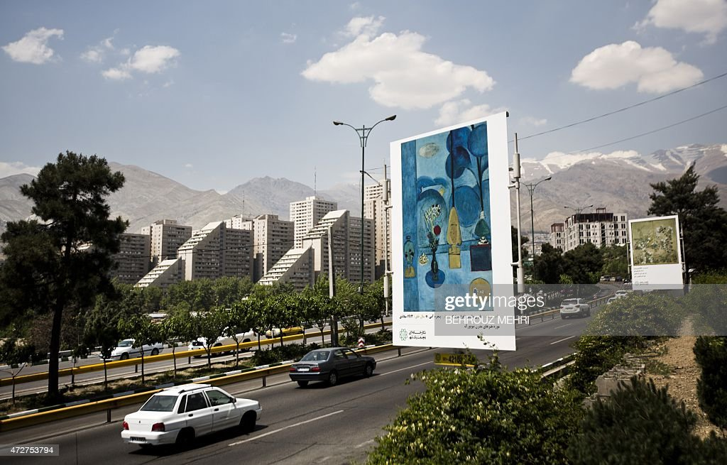 Cars drive past a billboard displaying the 'Blue Window' painting by French artist Henri Matisse on Tehran's Chamran highway on May 9 2015 More than...