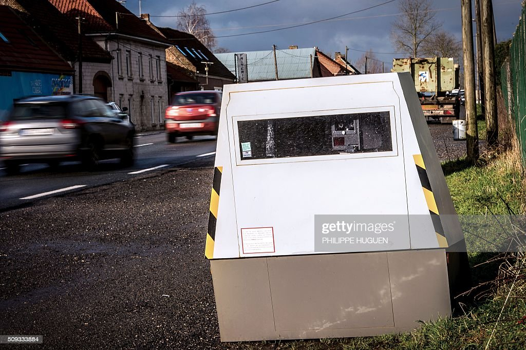 Cars drive past a speed camera on the D939 in Aubigny-en-Artois on February 10, 2016, in the first area in France to be outfitted with 'luring signs'. Eleven signs reading 'For your safety, frequent use of speed cameras' will be installed on a portion of the by-road in the Pas-de-Calais department, but a speed camera will be hidden behind only one of the signs, which will be moved regularly. / AFP / PHILIPPE HUGUEN