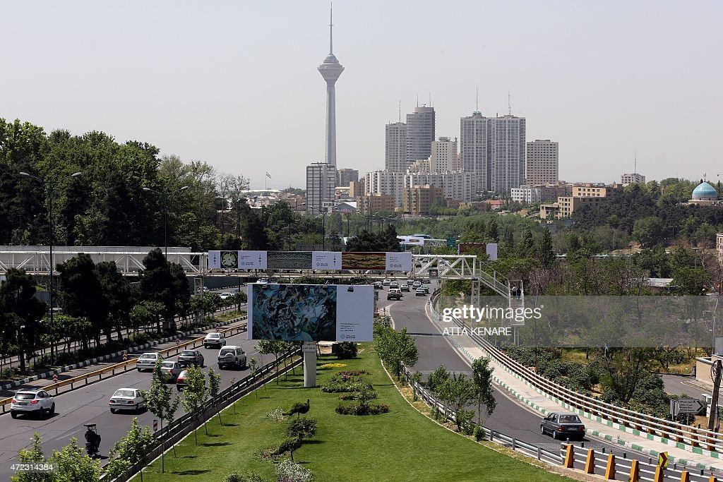 Cars drive past billboards in the Iranian capital Tehran on May 6 2015 displaying art pieces from local and foreign artists as well as reproductions...