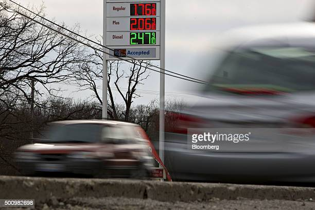 Cars drive past gas prices displayed on a sign outside a fueling station in Chilicothe Illinois US on Friday Dec 11 2015 The cost of a gallon of...